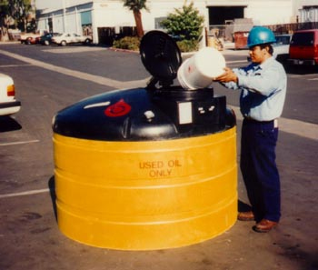 Man pouring waste oil in storage tank